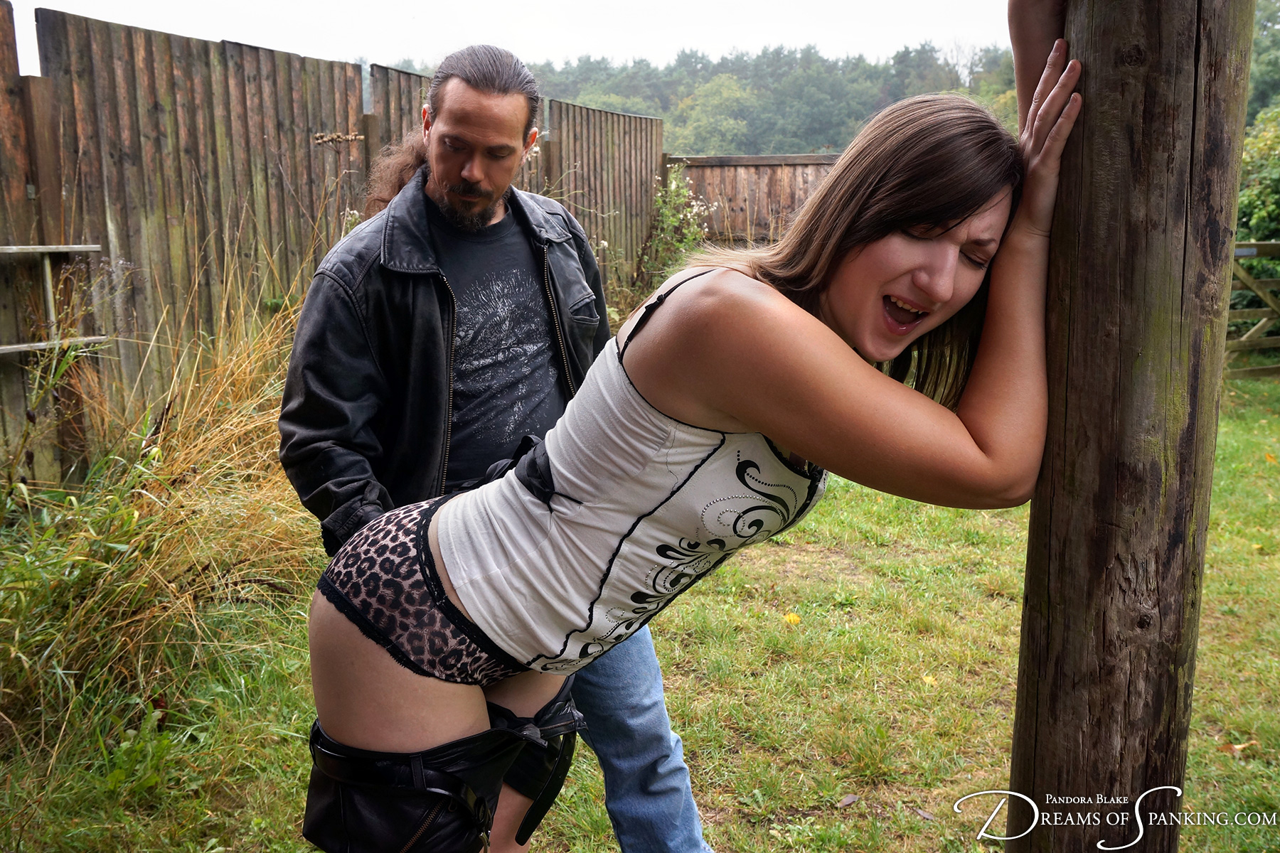 Pandora Blake strapped in leather shorts by Thomas Cameron at Dreams of Spanking