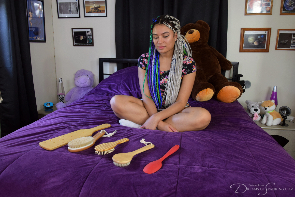 Jayda Blayze looks at the variety of spanking implements laid before her