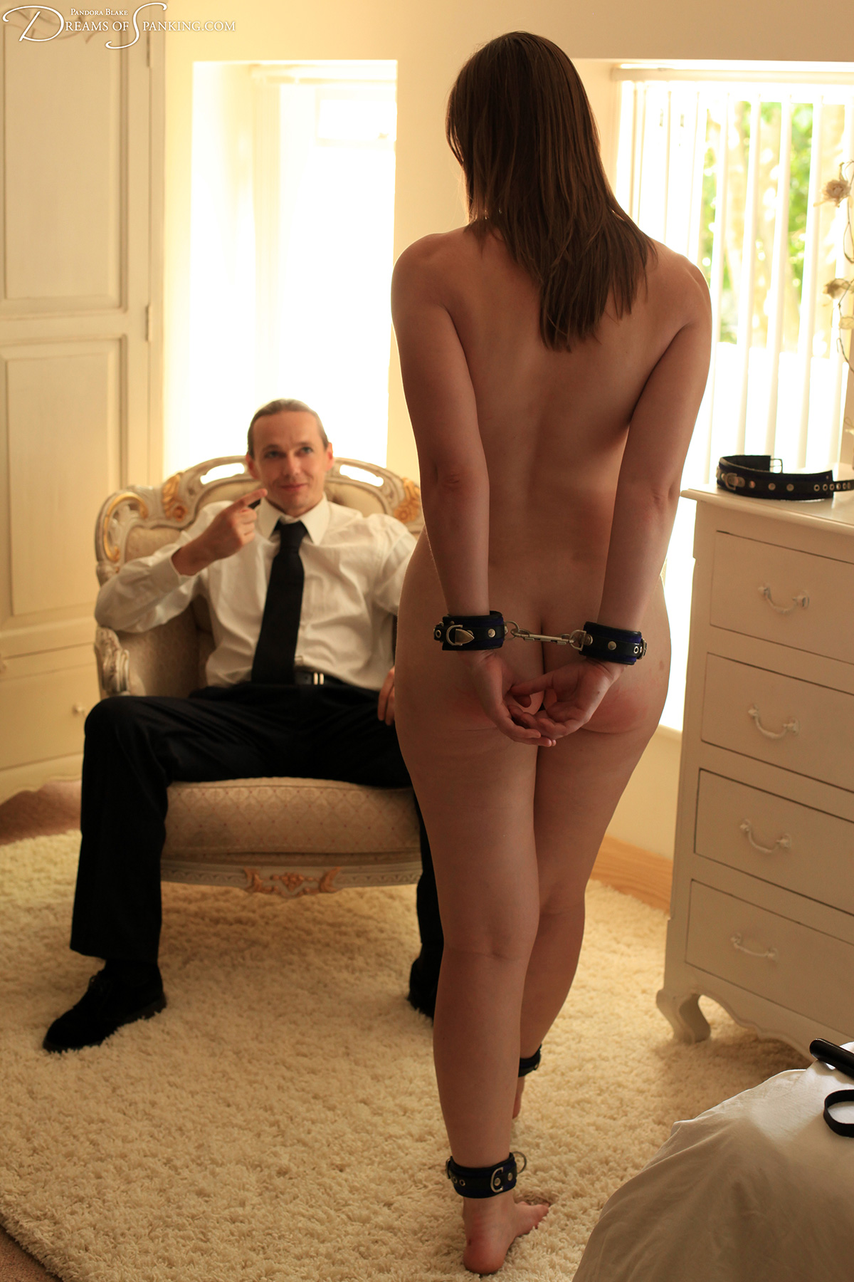 A naked, cuffed submissive walks towards her master as he beckons her to come closer.