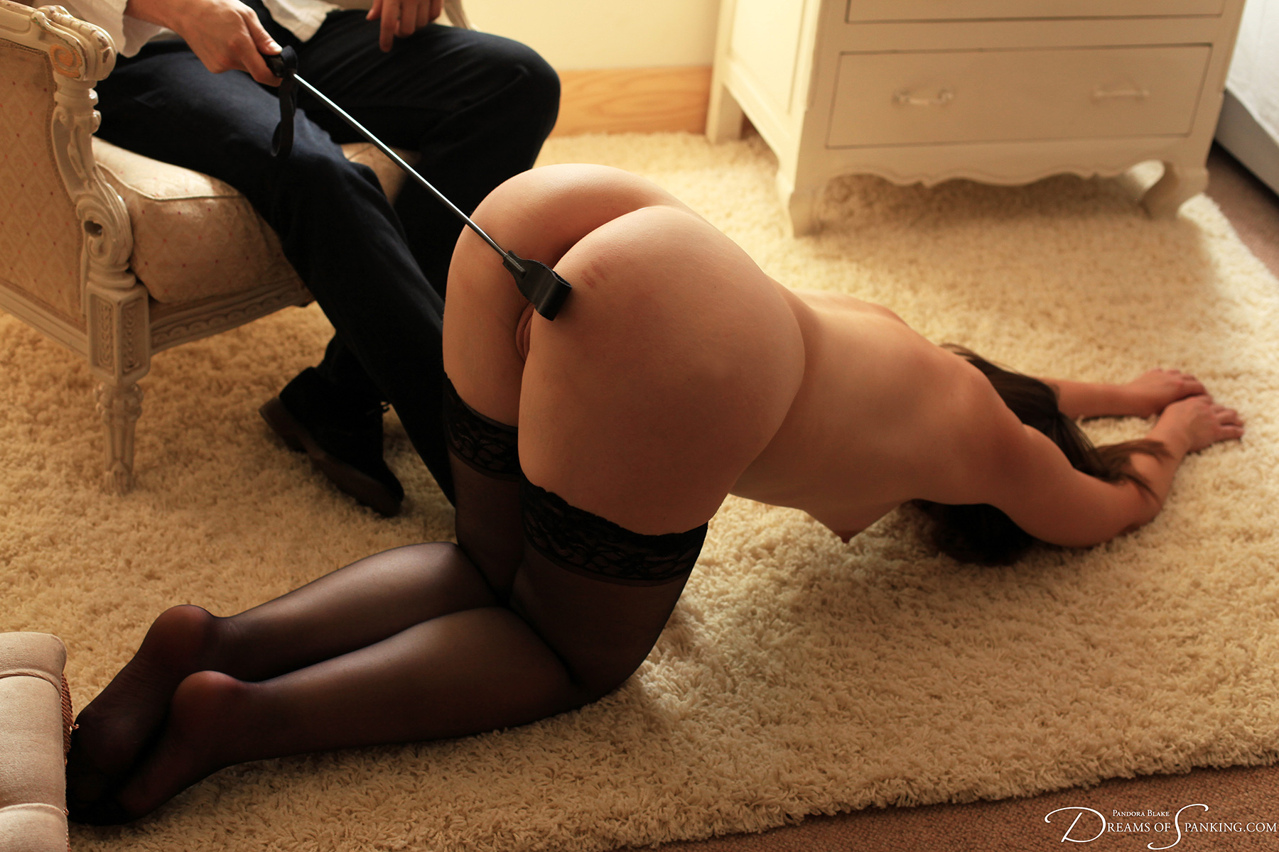 A naked woman surrenders and offers her bottom submissively to the crop.