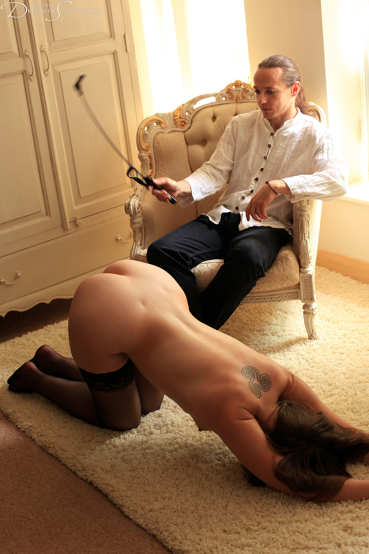 A naked girl on hands and knees submits to the sting of the crop.