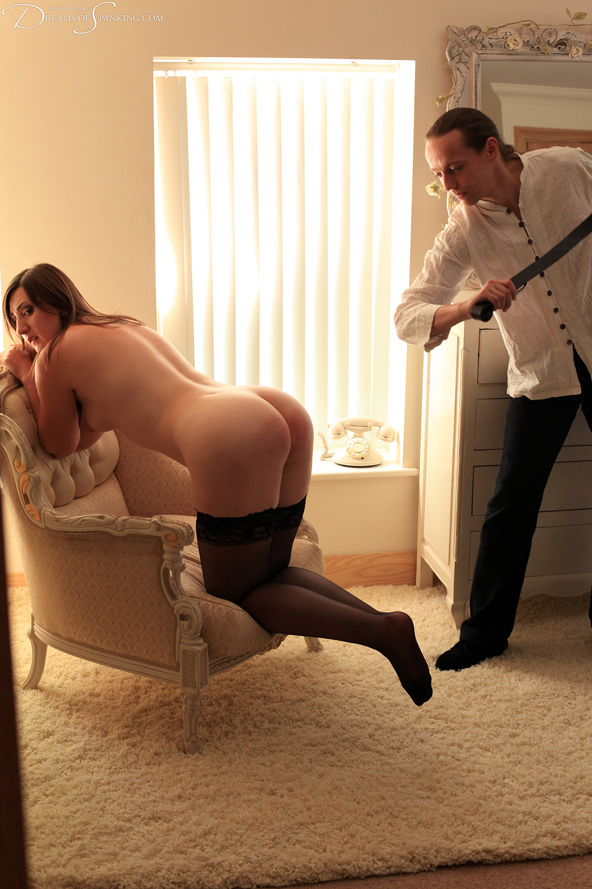 A naked submissive knees on a chair and offers her bottom to the belt.