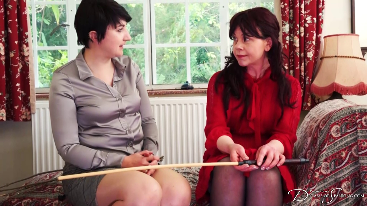 Emma Christie holds the cane and talks to Pandora Blake at Dreams of Spanking
