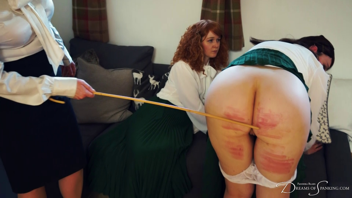 Pandora Blake gets the cane on her red, striped bottom as Faerie Willow watches at Dreams of Spanking