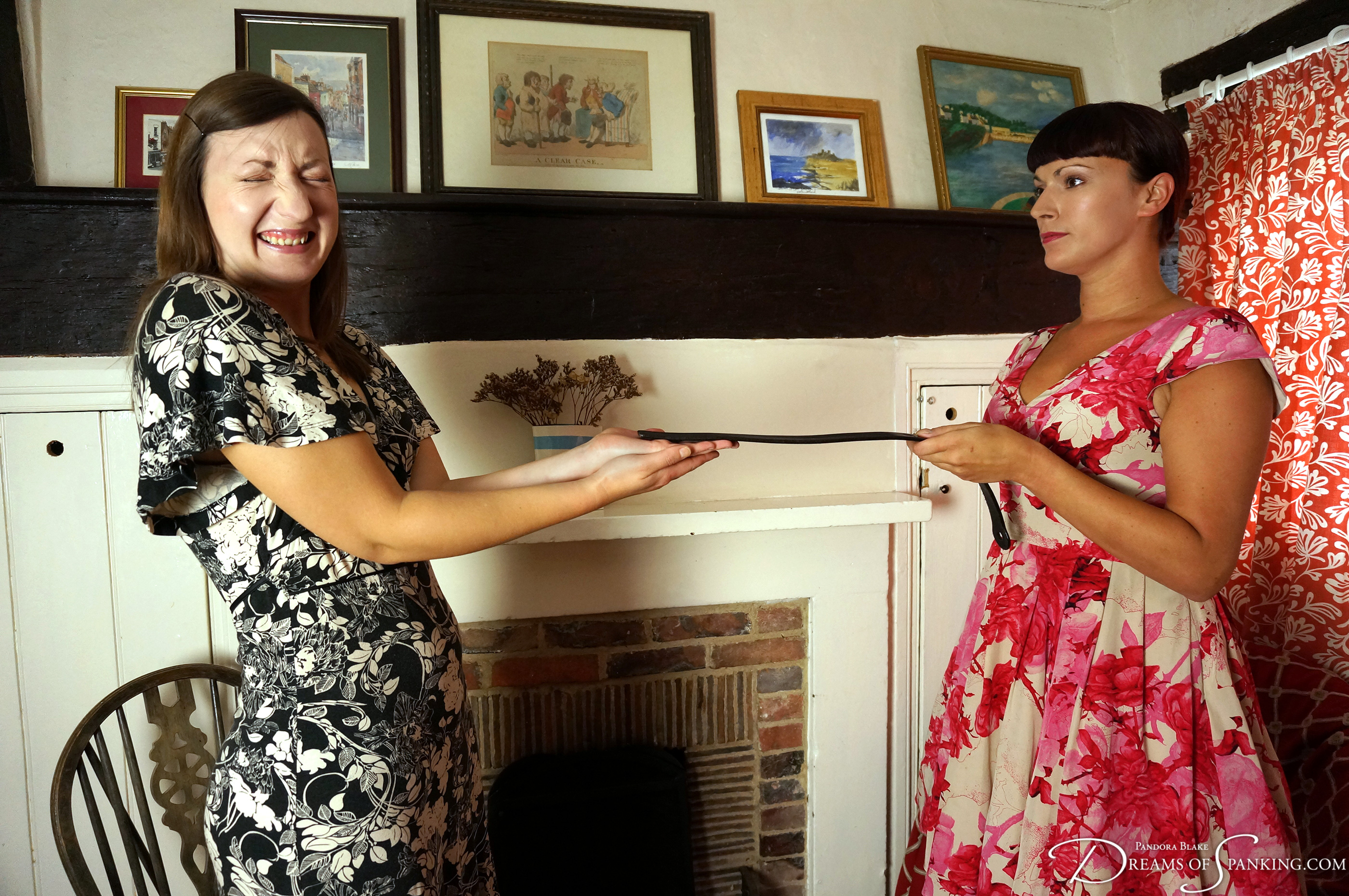 Pandora Blake holds out her hands for the tawse at Dreams of Spanking