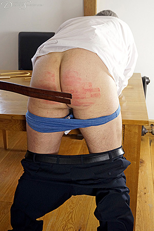 Headmaster Mike Pain instructs new teacher Pandora Blake in corporal punishment with the tawse at Dreams of Spanking