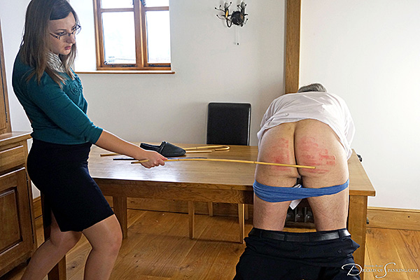 Headmaster Mike Pain instructs new teacher Pandora Blake in corporal punishment with the cane at Dreams of Spanking