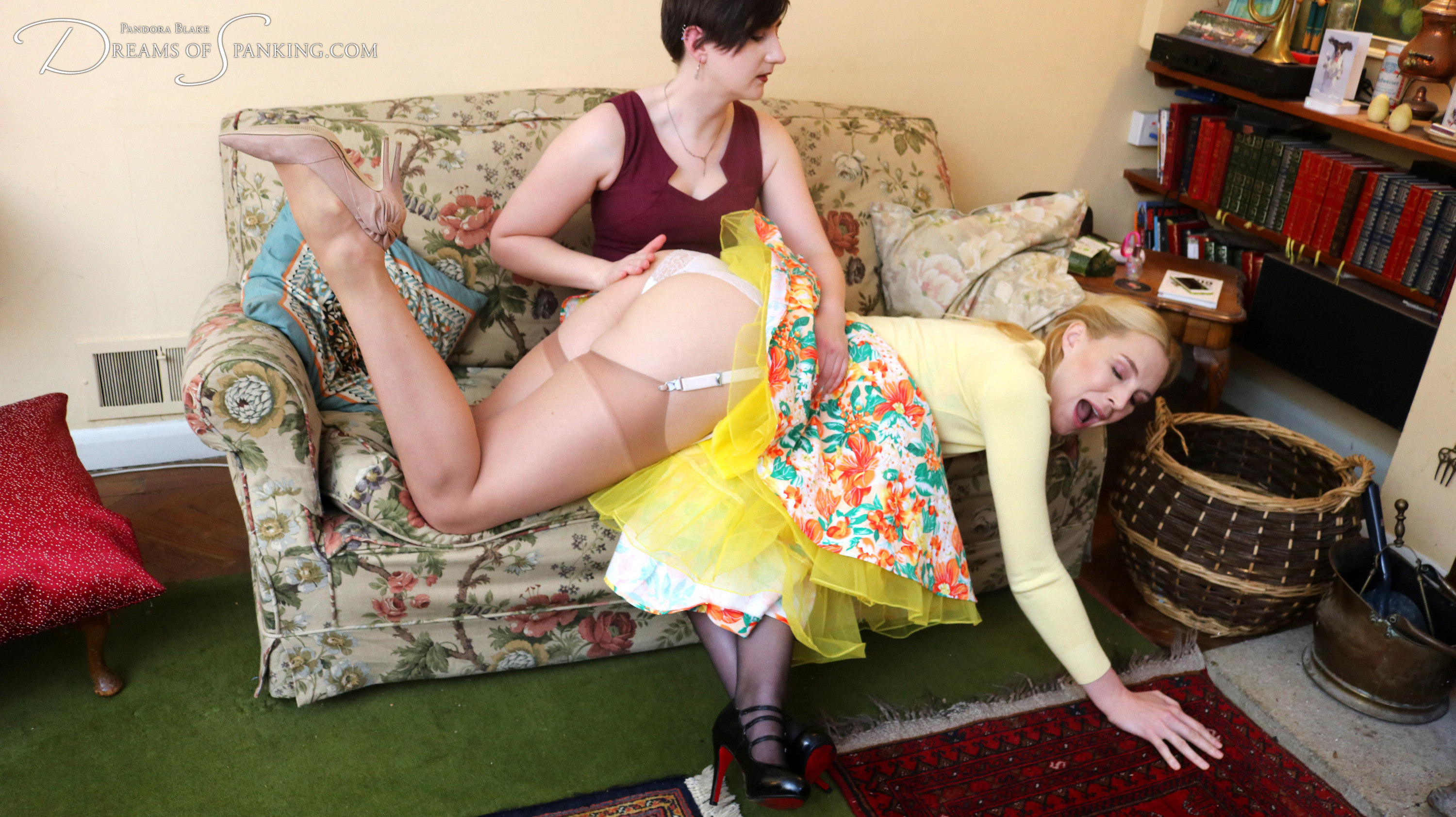 Amelia Jane Rutherford over Pandora Blake's knee for a spanking at Dreams of Spanking