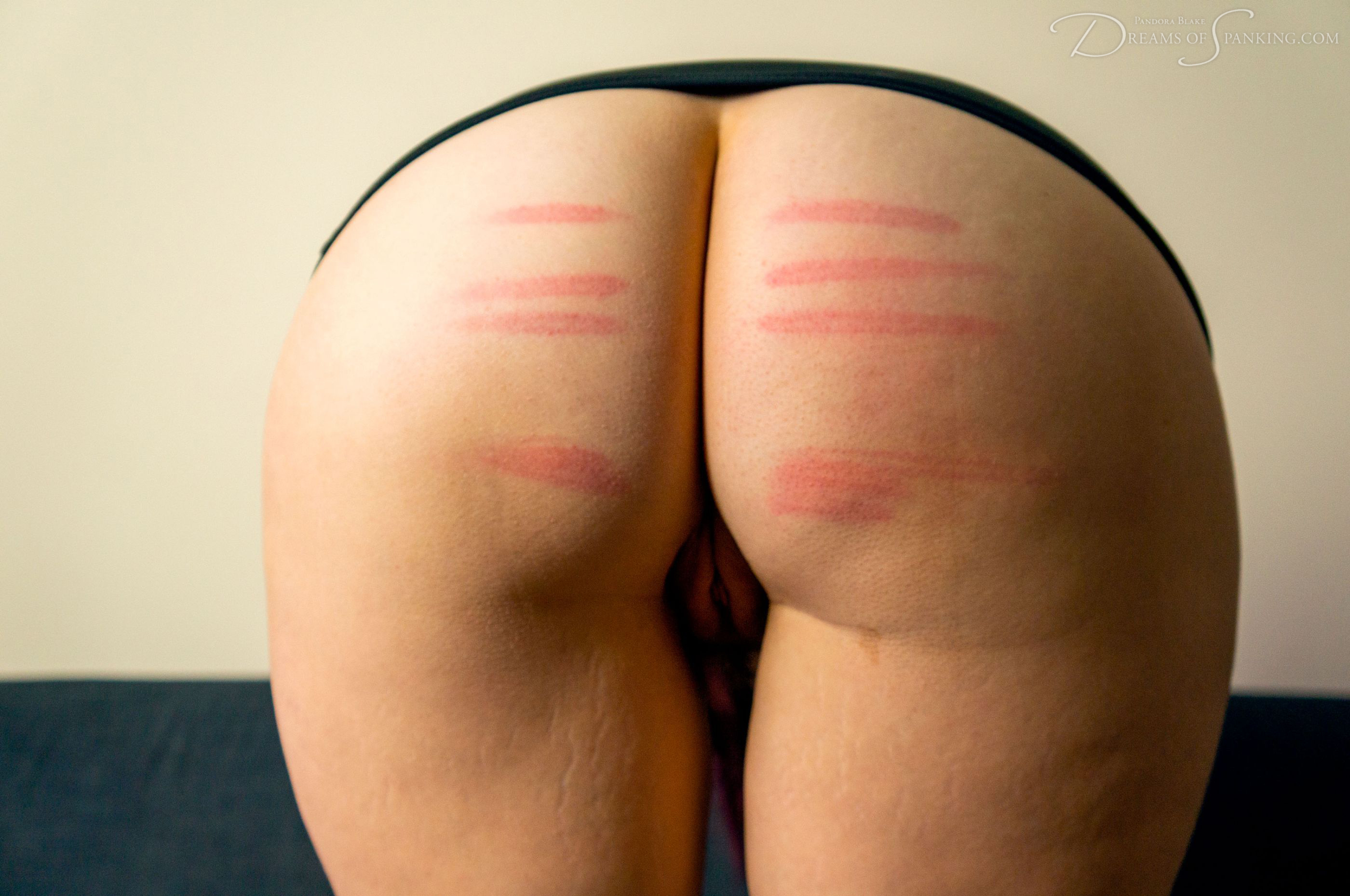 Pandora Blake's caned bare bottom at Dreams of Spanking