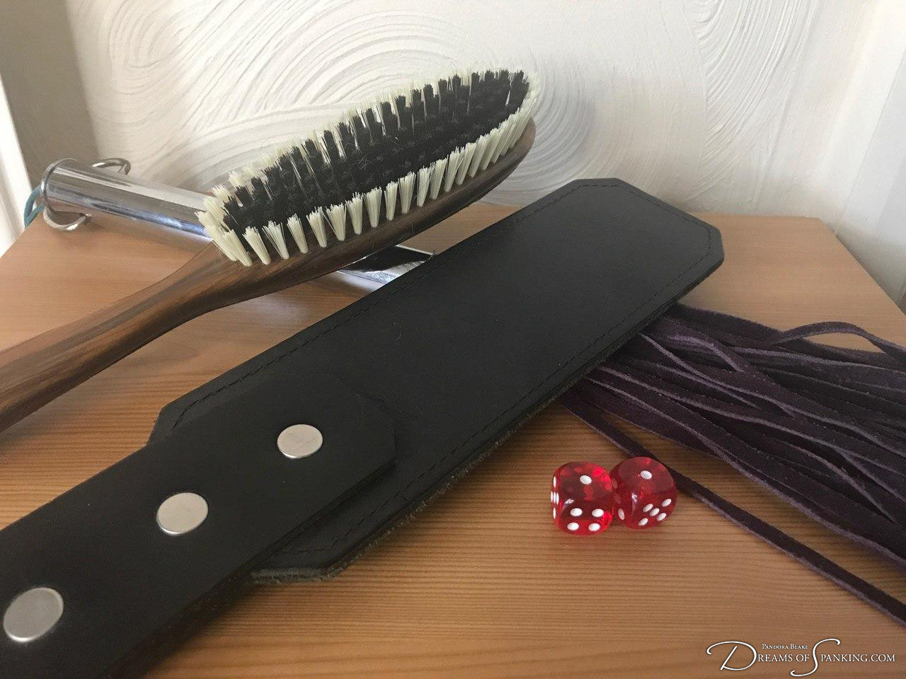Paddle, flogger and dice at Dreams of Spanking