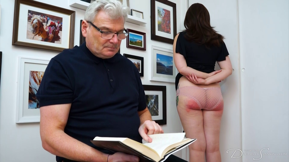 Pandora Blake stands in the corner, her spanked bare bottom on display while Stephen Lewis reads a book Dreams of Spanking