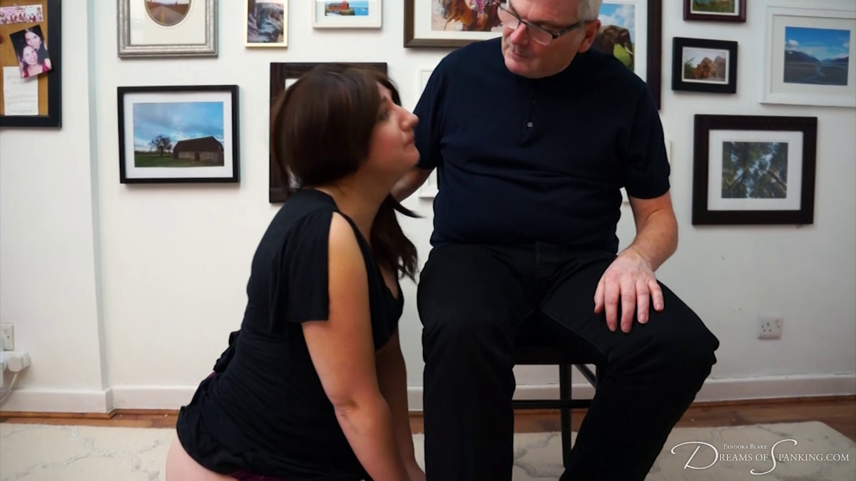 Pandora Blake kneels at Stephen Lewis's feet wearing her punishment dress at Dreams of Spanking