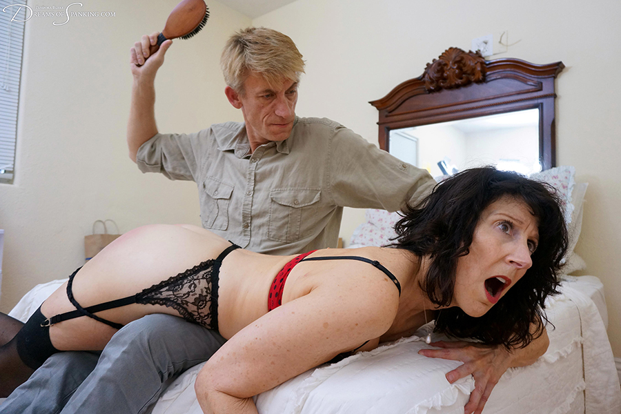 A hard strapping for spanked wife Erica Scott in sexy lingerie at Dreams of Spanking