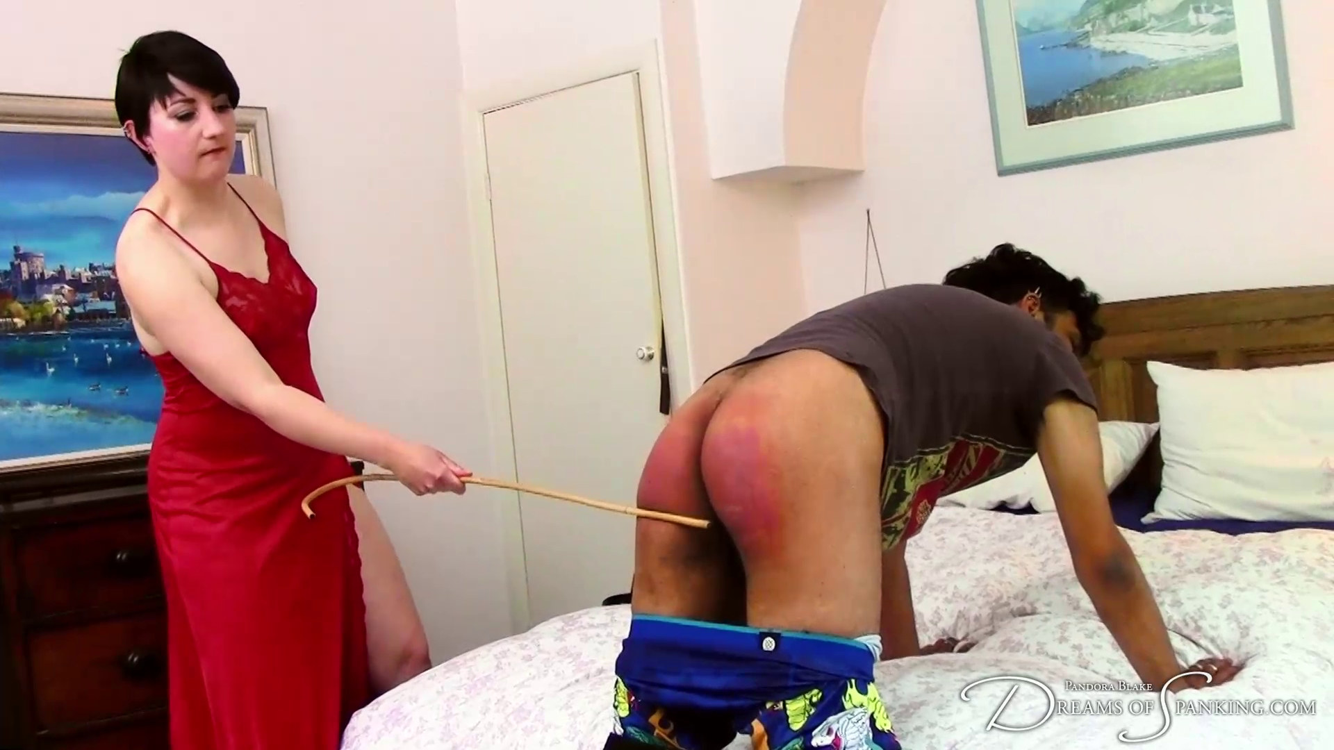 Carlos Green gets the cane on his red bottom from Pandora Blake at Dreams of Spanking